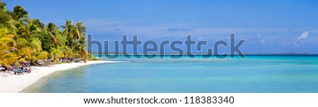 Beautiful beach at little tropical island in French Polynesia - stock photo