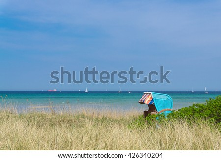 Beautiful beach chair in the dunes with the Baltic Sea sail ships in the background, Germany - stock photo
