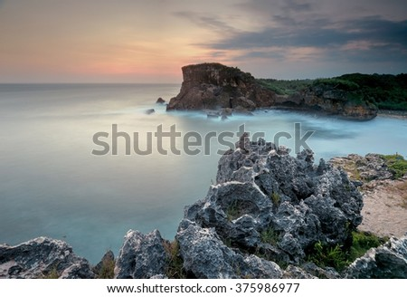 Beautiful beach in Gunung Kidul, Indonesia. Sunrise at the beautiful beach with green seaweeds  and rocks profile in the foreground.The image may have grain/noise/soft focus due to long exposure.