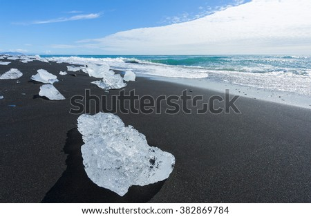 Beautiful beach in the South of Iceland with a black lava sand is full of icebergs from glaciers not far away