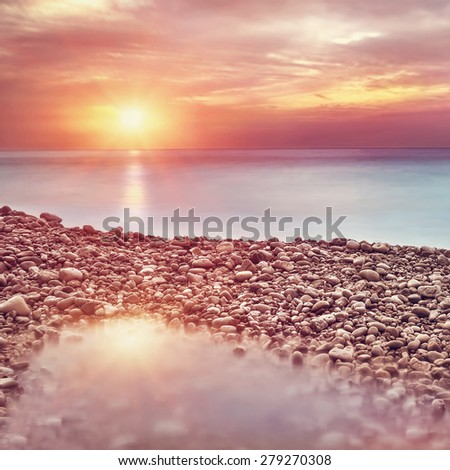Beautiful beach landscape in sunset light, amazing view on pebble coastline, romantic travel destination - stock photo