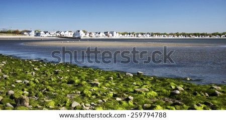 Beautiful beach landscape with homes in the distance - stock photo