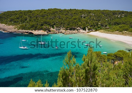 Beautiful beach of Cala Trebaluger with yacht and boats on turquoise sea water, Menorca, Balearic Islands, Spain