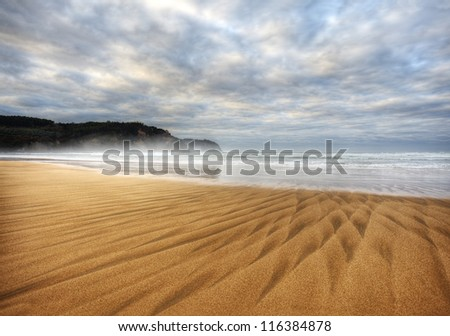 Beautiful beach of North Spain with waves  marks in the sand