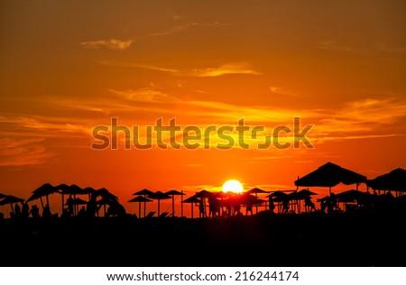 beautiful beach silhouettes of palm beach umbrella at sunset - stock photo