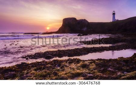 Beautiful beach sunset with lighthouse - stock photo