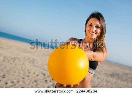 Beautiful beach volleyball female player serving ball. - stock photo