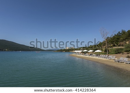 Beautiful beach with a sea view lagoon green forested hills - stock photo