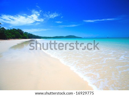 Beautiful beach with crystal clear blue waters of the Andaman sea against blue sky at Krabi bay, Thailand. - stock photo
