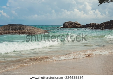 Beautiful beach with crystal clear blue waters of the Andaman sea with waves - stock photo