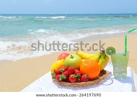 Beautiful beach with fresh fruits - stock photo