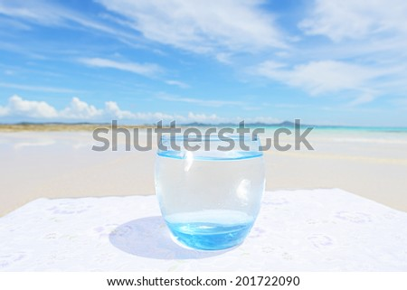 Beautiful beach with glass of water