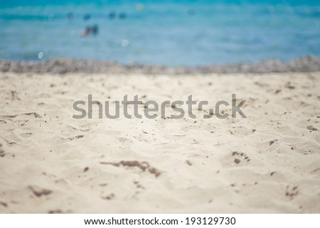 Beautiful beach with pebbles and buoy and chaise-longs on mediterranean sea with beautiful manual lens bokeh   - stock photo