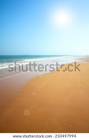 Beautiful beach with sand, blue waves and sky  - stock photo