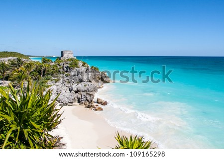 Beautiful beach with turquoise water  in Tulum Mexico, Mayan ruins on top of the cliff. - stock photo