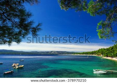 Beautiful beach Zlatni Rat or Golden Cape on island Brac in Croatia with yachts - stock photo