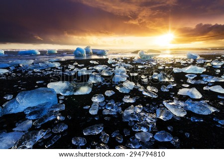 Beautiful beached chunks of ice at the beach at Jokulsarlon, Iceland, at sunset in winter - stock photo