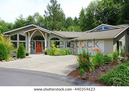 Beautiful beige house with white trim and driveway to garage decorated with flower bed.