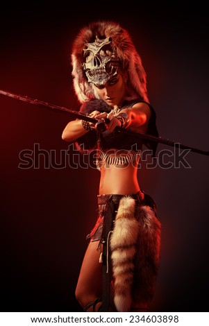 Beautiful bellicose Amazon with bow and arrows in battle. Ancient times. - stock photo