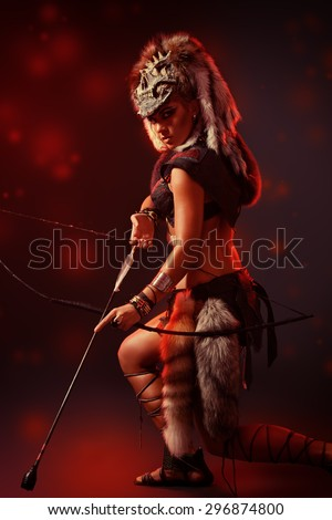 Beautiful bellicose Amazon with bow and arrows in battle. Ancient times.