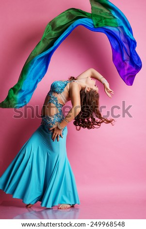 Beautiful belly dancer girl is wearing a blue fashion costume is dancing with shawl - stock photo
