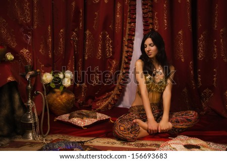 Beautiful belly dancer lying down in the arabic harem interior