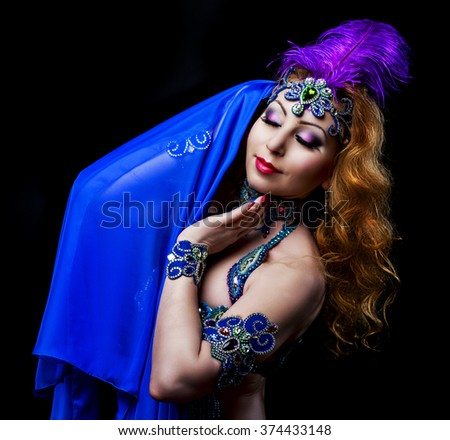 beautiful belly-dancer with long ginger hair and arabic makeup, isolated against black studio background - stock photo