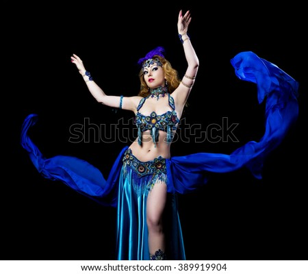 beautiful belly-dancer with long ginger hair and arabic makeup, isolated against  blue studio background - stock photo