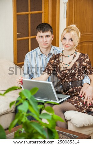 Beautiful beloved couple working on a laptop in his apartment. - stock photo