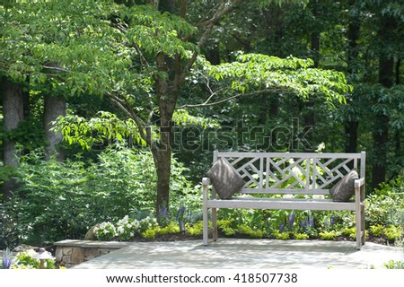 Beautiful bench outdoors surrounded by trees and flowers