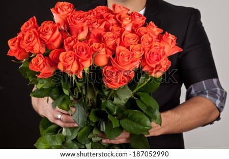 Beautiful big bouquet of red roses in man hands.  - stock photo