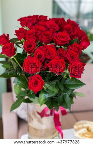 beautiful big bouquet of roses in a vase standing on the table