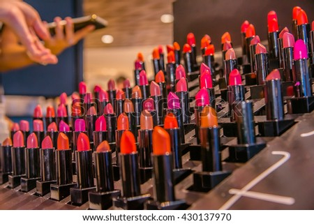 Beautiful big multicolor professional makeup set of many different colorful lipsticks in black plastic tubes in show case, horizontal picture, Selective Focus - stock photo