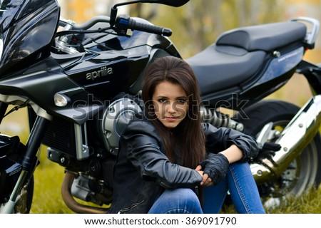 Beautiful biker girl,snorting biker girl,stunning biker girl,attractive biker girl,nice biker girl with leather jacket,modern,new,black motorcycle,motorbike,long hair,sitting on road near motorbike. - stock photo