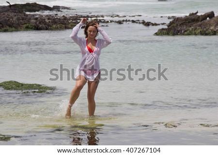 beautiful bikini babe enjoying the water by the sea shore - stock photo