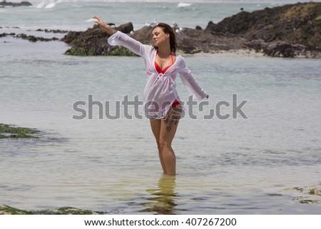 Beautiful bikini babe enjoying the water by the Seaside - stock photo