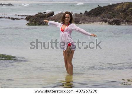 beautiful bikini babe enjoying the water by the Seaside while looking at camera - stock photo