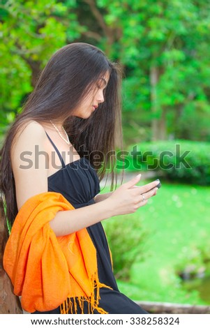 Beautiful biracial Asian Caucasian teen girl using cellphone with greenery in background, side profile - stock photo
