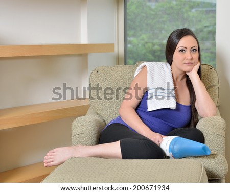 Beautiful biracial (Caucasian and Asian) woman resting on comfortable living room chair with small vacuum cleaner and towel - break from cleaning - stock photo