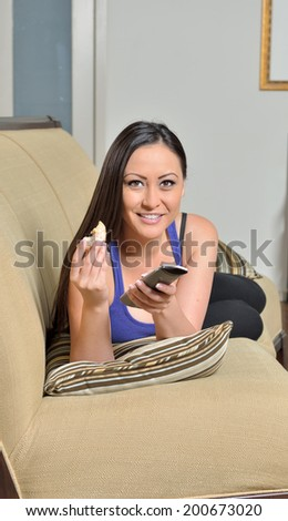Beautiful biracial (Caucasian and Asian) woman resting on comfortable living room couch wearing purple tank top - holding tv remote control and partially eaten donut  - stock photo