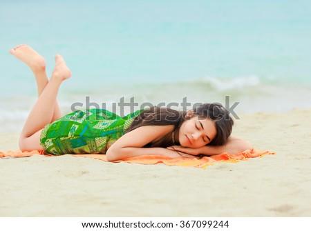 Beautiful biracial teen girl lying down on stomach sleeping  at tropical hawaiian beach with aqua blue ocean in background - stock photo