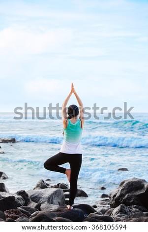 Beautiful biracial teen girl  standing on rock by ocean doing yoga - stock photo