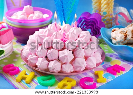beautiful birthday cake in ball shape decorated with pink meringue cookies and candles for girl