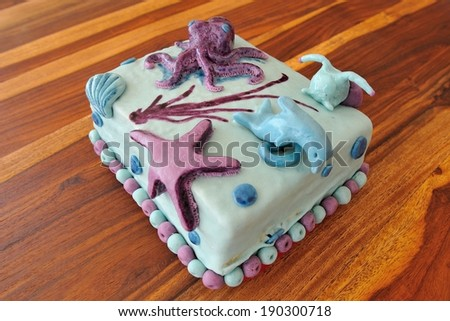 Beautiful birthday cake in submarine decoration with dolphin, octopus, snail and underwater star - stock photo