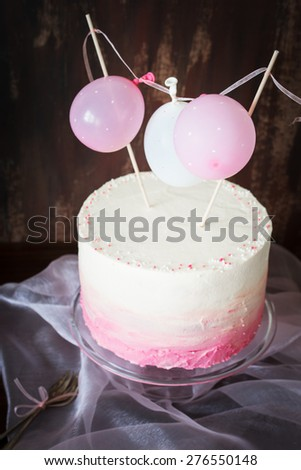 Beautiful birthday / wedding / baby shower cake with cream cheese frosting. Decorated with tiny balloons. Selective focus. - stock photo