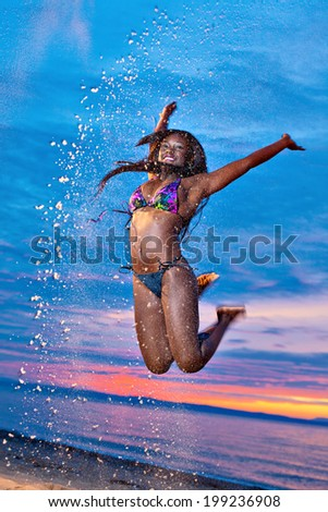 Beautiful black African American woman jumping up the air on the beach at sunset - stock photo