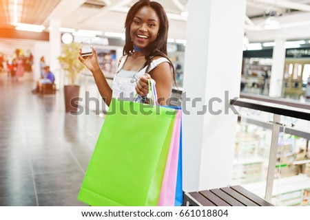 Beautiful black african american woman walking with colorful shopping bags in the mall.