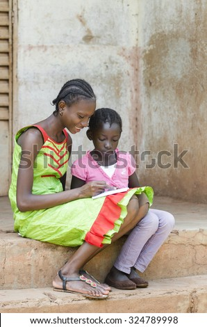 Beautiful black African school girls sitting on stairs with a light smile while writing a letter with lots of colors in the streets of the capital of Mali, Bamako. - stock photo