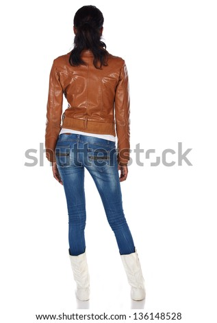 Beautiful black african young adult woman casually dressed in a brown leather jacket and Blue jeans with white boots and with her hair slicked back into a ponytail and isolated on a white background