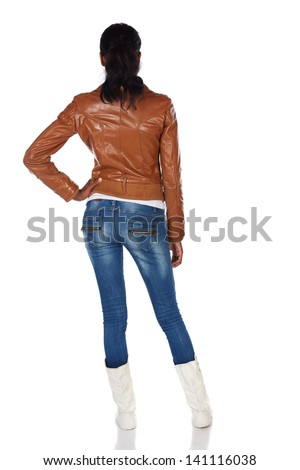 Beautiful black african young adult woman casually dressed in a brown leather jacket and Blue jeans with white boots and with her hair slicked back into a ponytail - hands on hips - stock photo